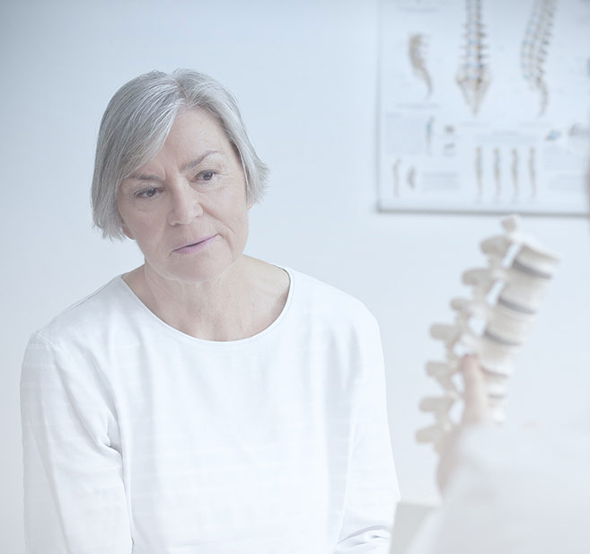 Image - Woman in doctor's office analyzing spine